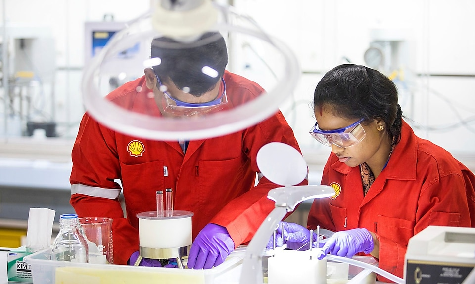 A woman Shell employee working with a man in a laboratory