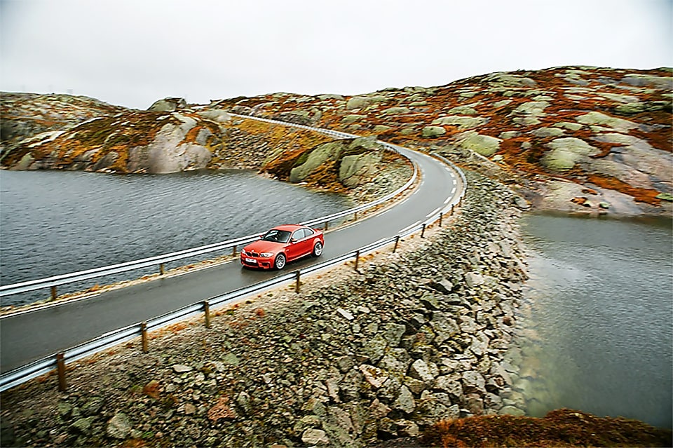running car on road with surrounding of mountains and sea